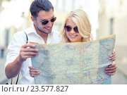 smiling couple in sunglasses with map in the city, фото № 23577827, снято 14 июля 2013 г. (c) Syda Productions / Фотобанк Лори