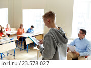 student boy with notebook and teacher at school, фото № 23578027, снято 22 апреля 2016 г. (c) Syda Productions / Фотобанк Лори