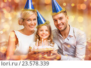 Купить «smiling family in blue hats with cake», фото № 23578339, снято 26 октября 2013 г. (c) Syda Productions / Фотобанк Лори