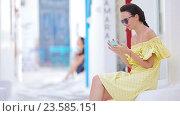 Купить «Красивая женщина с телефоном на открытом воздухе на старых улицах Миконоса», видеоролик № 23585151, снято 31 августа 2016 г. (c) Дмитрий Травников / Фотобанк Лори