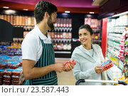 Купить «Smiling male staff assisting a woman with grocery shopping», фото № 23587443, снято 9 мая 2016 г. (c) Wavebreak Media / Фотобанк Лори