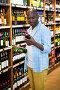 Man looking at wine bottle in grocery section, фото № 23587787, снято 9 мая 2016 г. (c) Wavebreak Media / Фотобанк Лори