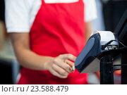 Купить «Female staff using credit card terminal at cash counter», фото № 23588479, снято 9 мая 2016 г. (c) Wavebreak Media / Фотобанк Лори