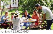 Купить «friends having barbecue party at summer garden», видеоролик № 23620643, снято 4 сентября 2016 г. (c) Syda Productions / Фотобанк Лори