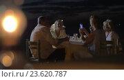 Купить «Family sitting at a table in evening in city Perea, Greece», видеоролик № 23620787, снято 5 февраля 2016 г. (c) Данил Руденко / Фотобанк Лори