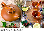 Herbal tea with herbs, lime and berries on a rustic wooden board. Стоковое фото, фотограф Tatjana Baibakova / Фотобанк Лори