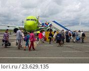 Пассажиры идут на посадку в самолет авиакомпании S7 по летному полю, аэропорт города Симферополь (2016 год). Редакционное фото, фотограф Вячеслав Палес / Фотобанк Лори