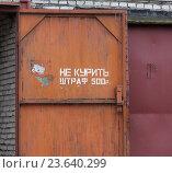 """Купить «Надпись """"Не курить"""", запрещающая курение под угрозой уплаты штрафа, на распахнутых красных железных воротах гаража», фото № 23640299, снято 24 сентября 2016 г. (c) Наталья Николаева / Фотобанк Лори"""