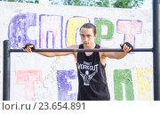 Купить «Подросток на турнике в майке с надписью street workout на фоне стены с надписью Спорт», фото № 23654891, снято 11 мая 2016 г. (c) Гетманец Инна / Фотобанк Лори