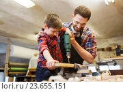 Купить «father and son with drill working at workshop», фото № 23655151, снято 14 мая 2016 г. (c) Syda Productions / Фотобанк Лори