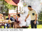 Купить «man cooking meat on barbecue grill at summer party», фото № 23655743, снято 28 августа 2016 г. (c) Syda Productions / Фотобанк Лори