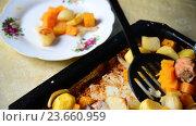 Купить «Homemaker puts in plate Baked potatoes with chicken and pumpkin», видеоролик № 23660959, снято 8 августа 2016 г. (c) Володина Ольга / Фотобанк Лори