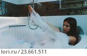 Купить «Happy girl taking bath full of foam in bathroom. Enjoy. Blow on soap foam.», видеоролик № 23661511, снято 25 августа 2016 г. (c) Александр Багно / Фотобанк Лори