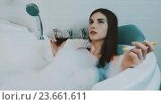 Купить «Girl taking bath full of foam. Smoke electronic cigarette, drink red wine.», видеоролик № 23661611, снято 26 августа 2016 г. (c) Александр Багно / Фотобанк Лори