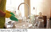 Купить «housewife in rubber gloves washing dishes», видеоролик № 23662975, снято 7 августа 2016 г. (c) Яков Филимонов / Фотобанк Лори