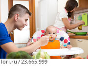 Купить «father feeding his baby and mother cooking at kitchen», фото № 23665999, снято 17 сентября 2014 г. (c) Оксана Кузьмина / Фотобанк Лори