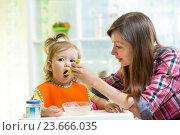 Купить «Mother feeding kid daughter at kitchen», фото № 23666035, снято 8 сентября 2014 г. (c) Оксана Кузьмина / Фотобанк Лори