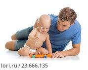 Купить «Father and baby boy having fun with musical toys. Isolated on white background», фото № 23666135, снято 6 сентября 2014 г. (c) Оксана Кузьмина / Фотобанк Лори