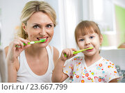 Купить «mother and child daughter brushing teeth in bathroom», фото № 23667799, снято 3 февраля 2014 г. (c) Оксана Кузьмина / Фотобанк Лори