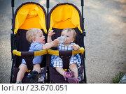 Купить «Близнецы в коляске. Мальчик помогает девочке пить из бутылочки», фото № 23670051, снято 19 июня 2016 г. (c) Вероника Галкина / Фотобанк Лори