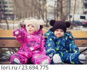 Близнецы сидят на скамейке в парке. Удивленная девочка указывает рукой на что-то. Стоковое фото, фотограф Вероника Галкина / Фотобанк Лори