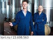 Two smiling men in uniforms standing in winery fermentation compartment. Стоковое фото, фотограф Яков Филимонов / Фотобанк Лори