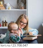 Купить «Мама и сын читают книгу дома», фото № 23708047, снято 14 октября 2015 г. (c) Кирилл Греков / Фотобанк Лори