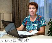 Купить «Пожилая женщина платит дома по счетам используя компьютер», эксклюзивное фото № 23708547, снято 19 июня 2016 г. (c) Вячеслав Палес / Фотобанк Лори