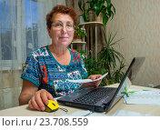 Пожилая женщина сидит дома за ноутбуком с квитанцией в руках. Стоковое фото, фотограф Вячеслав Палес / Фотобанк Лори