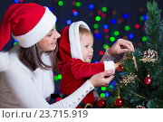 Купить «child girl with mother decorating Christmas tree on bright background», фото № 23715919, снято 14 октября 2012 г. (c) Оксана Кузьмина / Фотобанк Лори