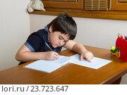 Купить «Мальчик переписывает домашнее здание в тетрадь», фото № 23723647, снято 20 февраля 2016 г. (c) Emelinna / Фотобанк Лори