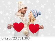Купить «smiling couple in winter clothes with red hearts», фото № 23731303, снято 8 октября 2015 г. (c) Syda Productions / Фотобанк Лори