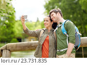 couple with backpacks taking selfie by smartphone, фото № 23731835, снято 27 мая 2016 г. (c) Syda Productions / Фотобанк Лори