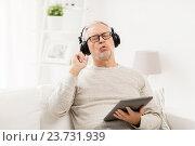 Купить «senior man with tablet pc and headphones at home», фото № 23731939, снято 7 июля 2016 г. (c) Syda Productions / Фотобанк Лори