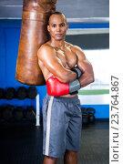 Купить «Confident male boxer standing by punching bag», фото № 23764867, снято 24 апреля 2016 г. (c) Wavebreak Media / Фотобанк Лори