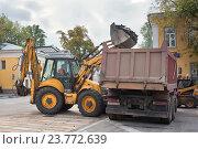 Трактор с ковшом грузит куски разбитого асфальта в кузов большого грузовика на московской улице (2016 год). Редакционное фото, фотограф Наталья Николаева / Фотобанк Лори