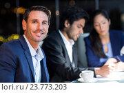 Купить «Businessman smiling at camera while colleagues interacting in the background», фото № 23773203, снято 16 февраля 2019 г. (c) Wavebreak Media / Фотобанк Лори