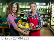 Купить «Female staff holding basket of fruits and male staff with clipboard in supermarket», фото № 23784235, снято 17 мая 2016 г. (c) Wavebreak Media / Фотобанк Лори
