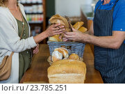 Купить «Mid section of woman purchasing bread at bakery store», фото № 23785251, снято 17 мая 2016 г. (c) Wavebreak Media / Фотобанк Лори