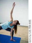 Купить «Woman performing extended side angle pose on exercise mat», фото № 23789935, снято 28 апреля 2016 г. (c) Wavebreak Media / Фотобанк Лори