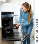 Купить «Woman placing roasting tray in kitchen oven», фото № 23790383, снято 16 декабря 2018 г. (c) Яков Филимонов / Фотобанк Лори