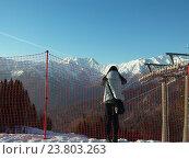 Купить «Девушка смотрит на снежные горные вершины», фото № 23803263, снято 1 апреля 2016 г. (c) DiS / Фотобанк Лори