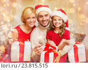 Купить «smiling family holding gift boxes and sparkles», фото № 23815515, снято 26 октября 2013 г. (c) Syda Productions / Фотобанк Лори