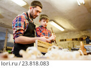 Купить «father and son with chisel working at workshop», фото № 23818083, снято 14 мая 2016 г. (c) Syda Productions / Фотобанк Лори