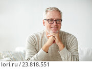 Купить «smiling senior man in glasses sitting on sofa», фото № 23818551, снято 7 июля 2016 г. (c) Syda Productions / Фотобанк Лори