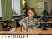 Купить «Мальчик делает ход при игре в шахматы», фото № 23822943, снято 17 сентября 2019 г. (c) Дмитрий Чемерик / Фотобанк Лори