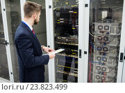 Купить «Technician holding clipboard while analyzing server», фото № 23823499, снято 13 апреля 2016 г. (c) Wavebreak Media / Фотобанк Лори
