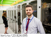 Купить «Smiling technician standing in a server room», фото № 23824095, снято 13 апреля 2016 г. (c) Wavebreak Media / Фотобанк Лори