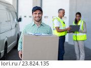 Купить «Portrait of delivery man carrying cardboard box», фото № 23824135, снято 23 марта 2016 г. (c) Wavebreak Media / Фотобанк Лори