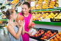 Mother with girl taking peaches on market, фото № 23874983, снято 21 октября 2016 г. (c) Яков Филимонов / Фотобанк Лори